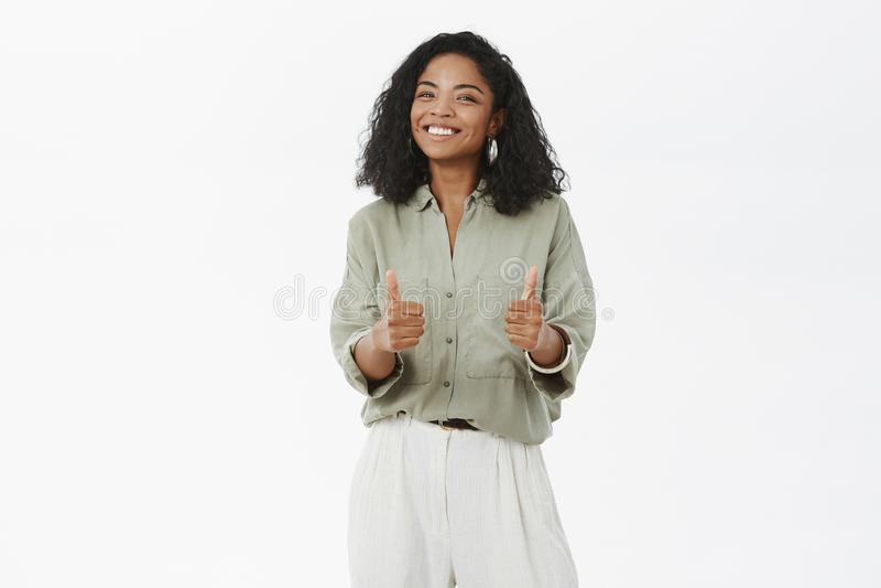 Retrato de la mujer afroamericana carismática divertida y entretenida con el peinado rizado que muestra los pulgares para arriba  imágenes de archivo libres de regalías