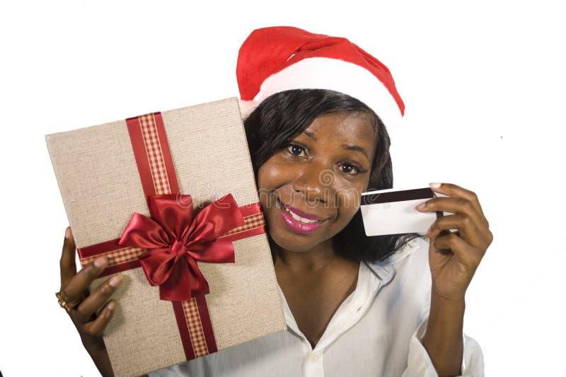 Retrato de la mujer afroamericana negra feliz y hermosa joven en el sombrero de Santa Claus que sostiene la actual tarjeta de la  fotos de archivo libres de regalías