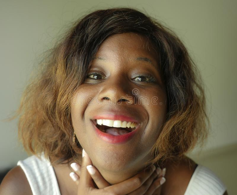Retrato de la mujer afroamericana negra feliz y hermosa joven que plantea la mirada alegre sonriente encantadora y juguetona a la fotos de archivo