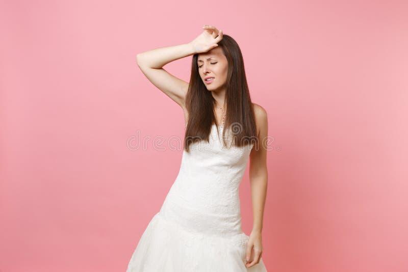 Retrato de la mujer agotada de la novia en el vestido que se casa blanco que mantiene la mano en la frente cansada de la preparac fotos de archivo libres de regalías
