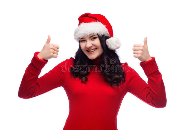 Retrato de la mujer alegre morena que lleva el sombrero de santa que sonríe y que aumenta su pulgar para arriba, el concepto de é imagen de archivo