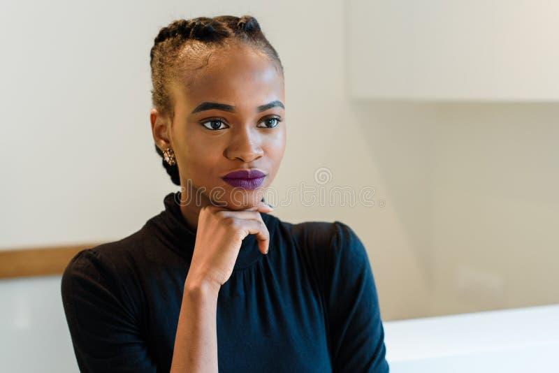 Retrato de la mujer americana africana o negra elegante confiada que sostiene la barbilla con la mano que piensa y que mira lejos imagen de archivo
