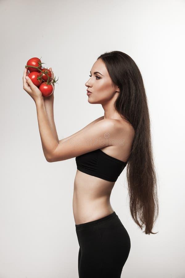 Retrato de la mujer apta de los jóvenes que sostiene los tomates rojos brillantes imagen de archivo