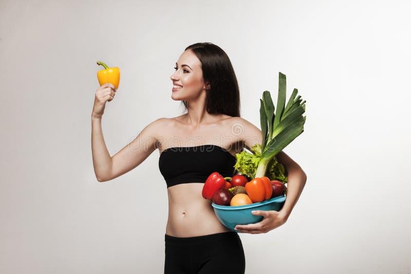 Retrato de la mujer apta de los jóvenes que sostiene verduras foto de archivo