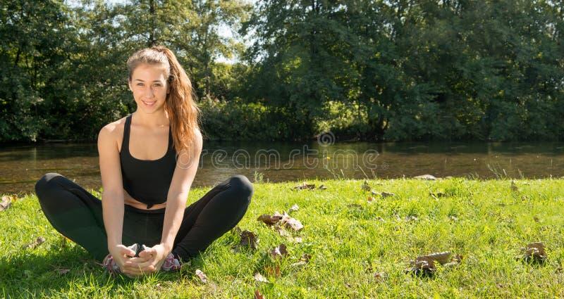 Retrato de la mujer apta de los jóvenes que se sienta en la hierba fotografía de archivo