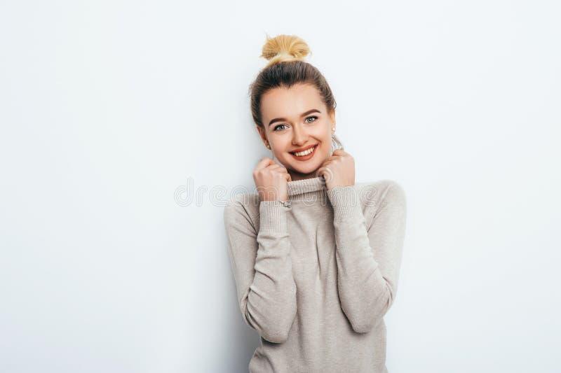 Retrato de la mujer apuesta alegre con sonrisa atractiva, comiendo el bollo del pelo que lleva en el suéter aislado sobre el fond foto de archivo