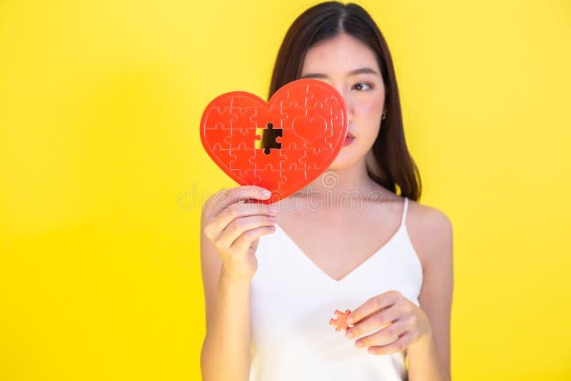 Retrato de la mujer asiática atractiva que sostiene el rompecabezas rojo del papel del corazón en fondo rosado foto de archivo