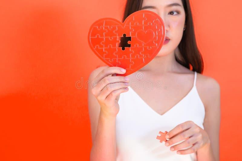 Retrato de la mujer asiática atractiva que sostiene el rompecabezas rojo del papel del corazón en fondo rosado fotografía de archivo