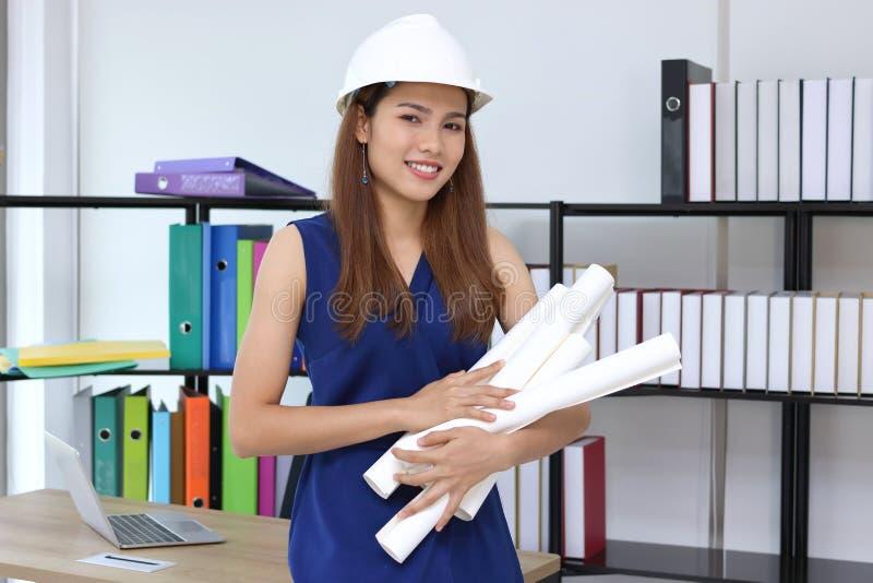Retrato de la mujer asiática confiada del ingeniero con el papeleo que se coloca en el lugar de trabajo de la oficina fotografía de archivo