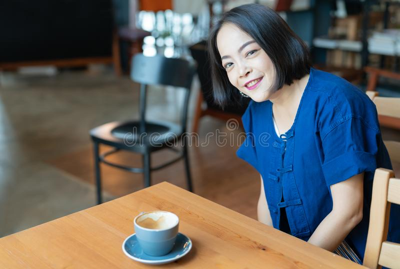 Retrato de la mujer asiática feliz con los ojos de la sonrisa, disfrutando del aroma fuerte sabroso del café de la mañana imagenes de archivo