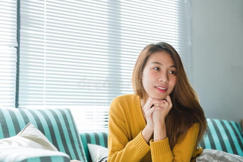 Retrato de la mujer asiática feliz del dueño casero con sentarse sonriente de los dientes perfectos en el sofá en la sala de esta fotos de archivo libres de regalías