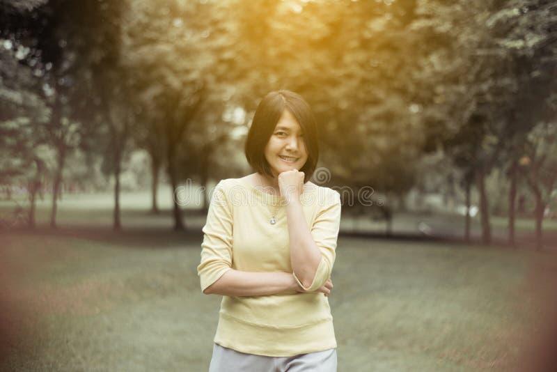 Retrato de la mujer asiática hermosa del pelo corto que se coloca en al aire libre por la mañana, feliz y sonriendo, pensamiento  imagenes de archivo