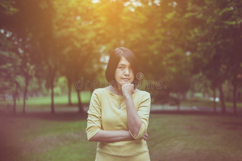 Retrato de la mujer asiática hermosa del pelo corto que se coloca en al aire libre por la mañana, feliz y sonriendo, pensamiento  fotografía de archivo