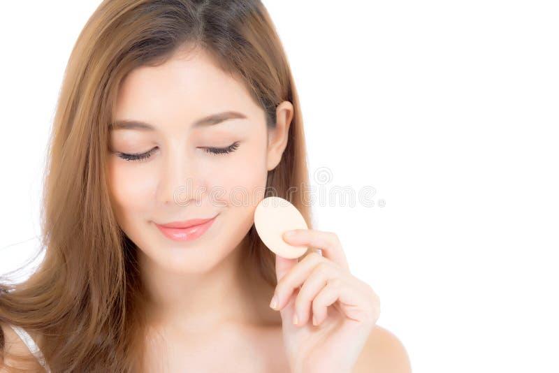 Retrato de la mujer asiática hermosa que aplica el soplo de polvo en el maquillaje de la mejilla del cosmético fotografía de archivo