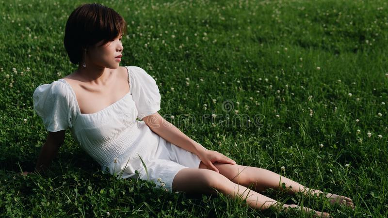 Retrato de la mujer asiática hermosa que se sienta en prados en el bosque del verano, muchacha china en el vestido blanco que due foto de archivo