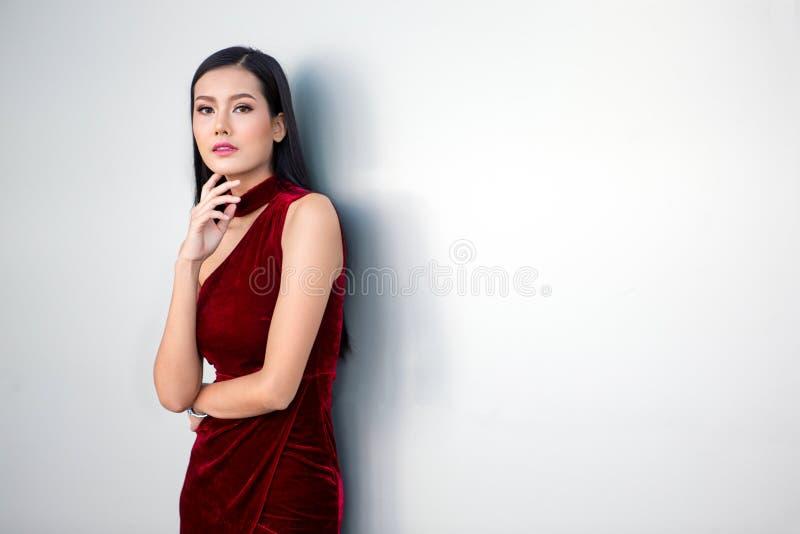 Retrato de la mujer asiática joven hermosa en un vestido rojo que presenta con la mano en la barbilla y que mira lejos en el fond imagen de archivo libre de regalías
