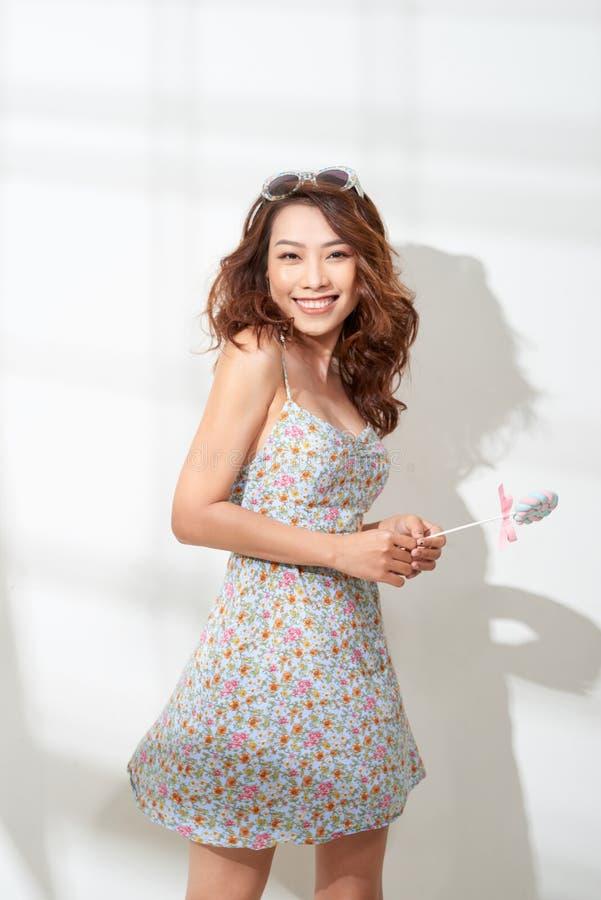Retrato de la mujer asiática joven linda elegante que sostiene la piruleta rosada grande imagenes de archivo