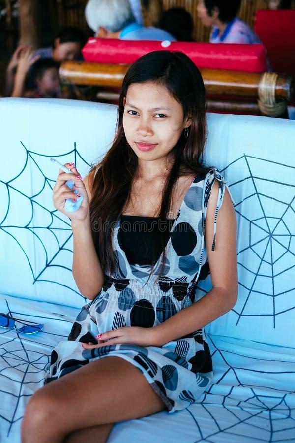 Retrato de la mujer asiática joven que fuma en la barra foto de archivo libre de regalías