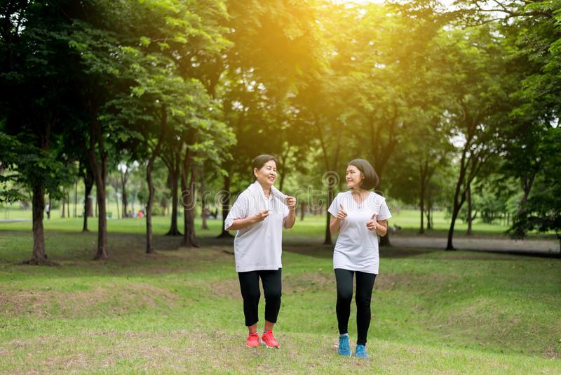 Retrato de la mujer asiática mayor con la hija que corre en el parque en madrugada concepto junto, sano y de la toma del cuidado fotografía de archivo