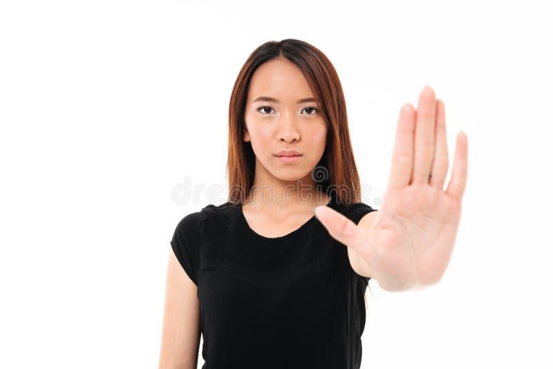 Retrato de la mujer asiática seria que se coloca con la mano extendida foto de archivo