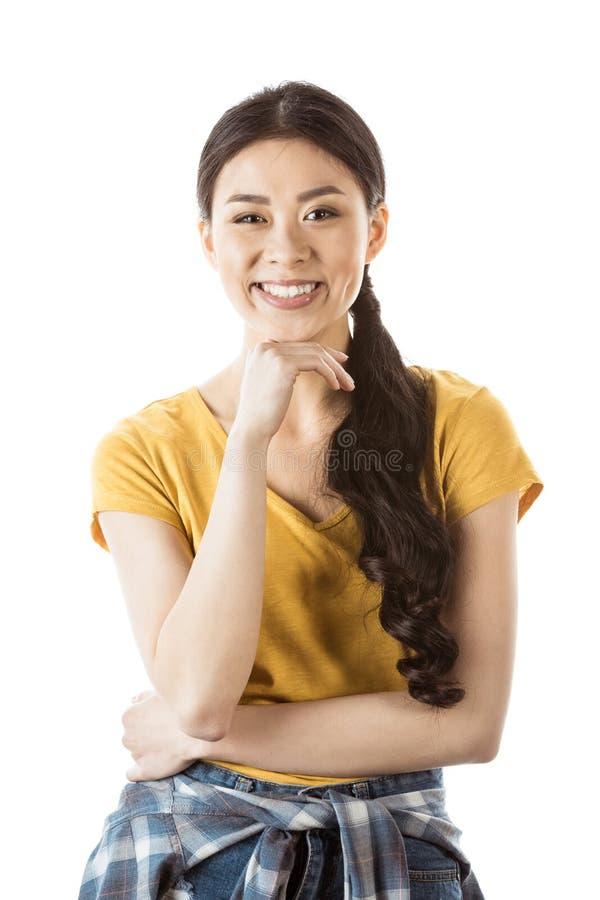 Retrato de la mujer asiática sonriente con la mano en la barbilla imagen de archivo
