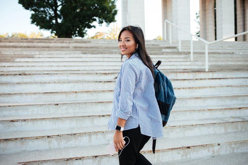 Retrato de la mujer asiática sonriente hermosa con la mochila que sube fotografía de archivo libre de regalías