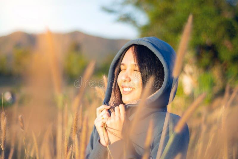 Retrato de la mujer asi?tica joven hermosa que disfruta de la naturaleza en prado de la hierba en la salida del sol foto de archivo
