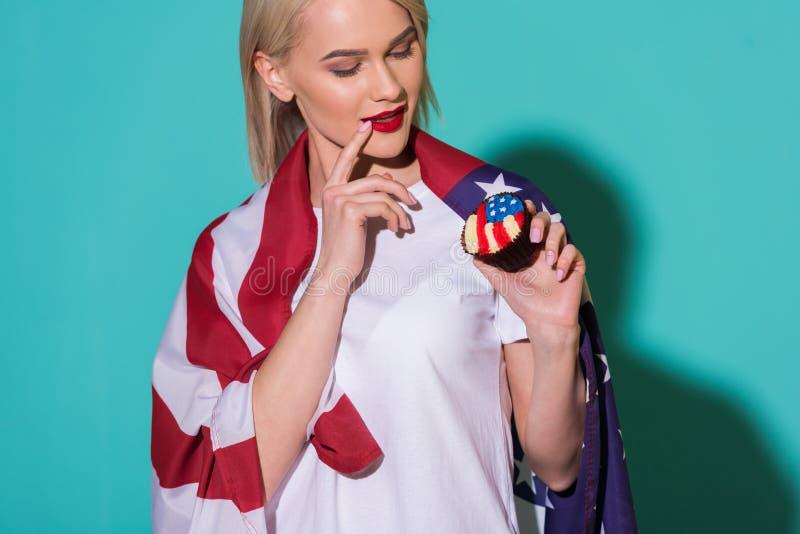 retrato de la mujer atractiva con la bandera americana y de la magdalena en el contexto azul que celebran 4to imagen de archivo libre de regalías