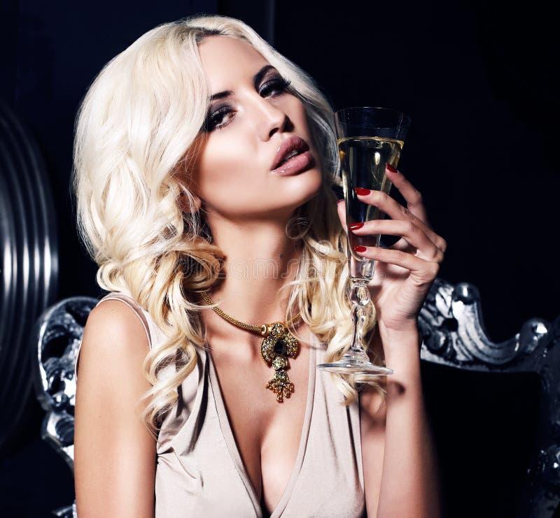 Retrato de la mujer atractiva con el pelo rubio con el vidrio de champán fotografía de archivo