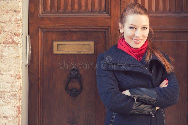 Retrato de la mujer atractiva delante de la puerta de madera vieja fotografía de archivo