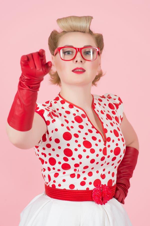 Retrato de la mujer atractiva en guantes rojos y vidrios rojos Muchacha hermosa que señala a usted por las manos en guantes rojos fotografía de archivo
