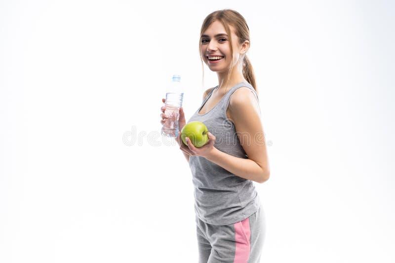Retrato de la mujer atractiva joven con la manzana y la botella verdes Concepto de dieta Aislado en blanco fotos de archivo libres de regalías