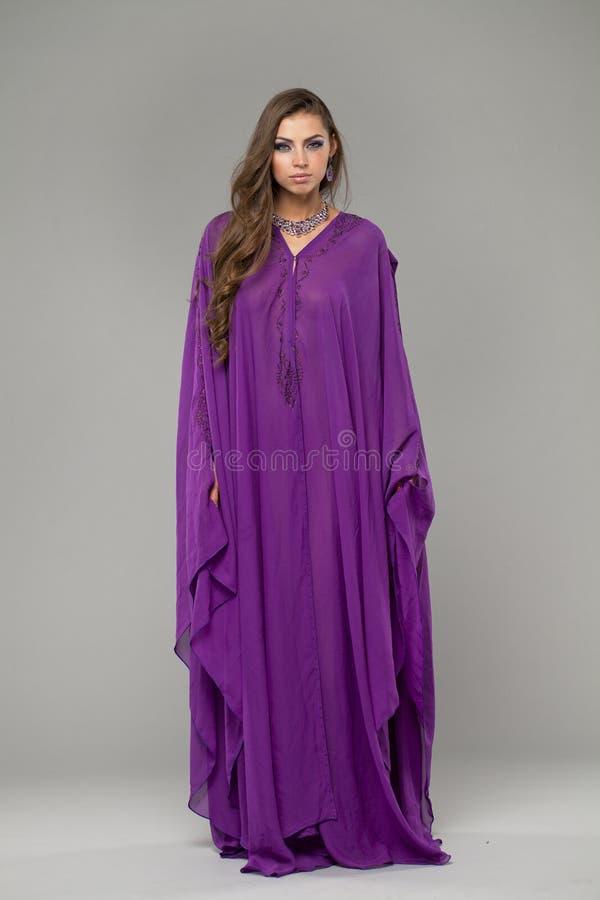 Retrato de la mujer atractiva joven en árabe púrpura de la túnica imagenes de archivo