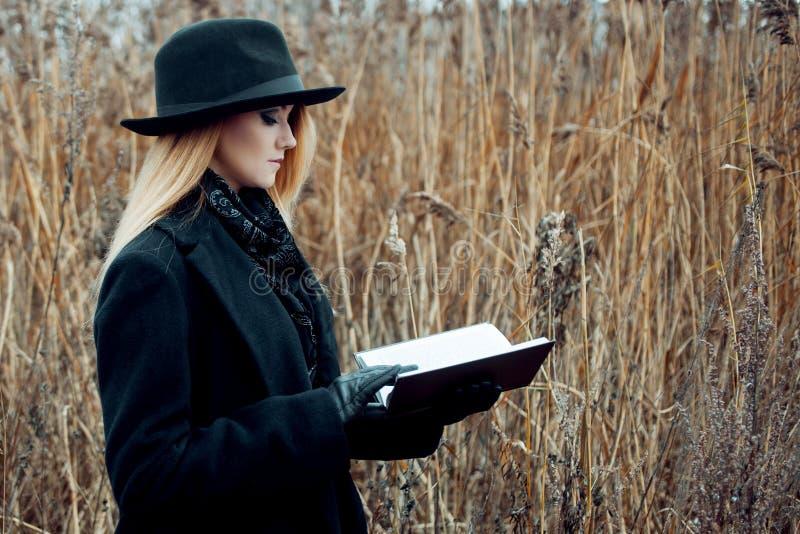 Retrato de la mujer atractiva joven en capa y sombrero negros Ella es una en un libro de lectura del campo, paisaje del otoño, hi foto de archivo