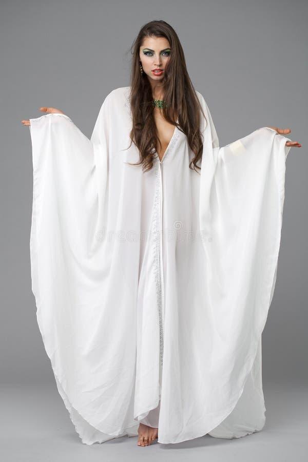Retrato de la mujer atractiva joven en un árabe blanco de la túnica fotografía de archivo