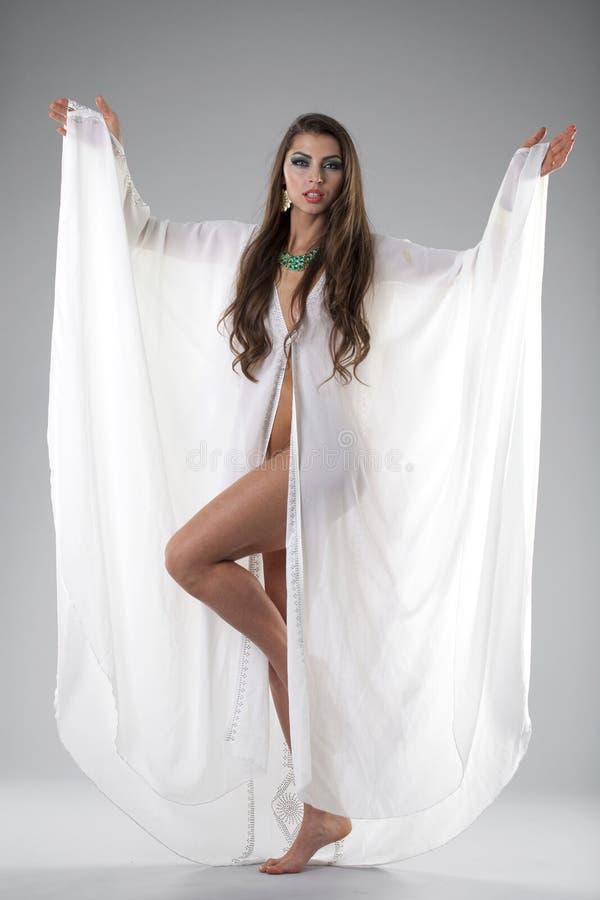 Retrato de la mujer atractiva joven en un árabe blanco de la túnica imagen de archivo
