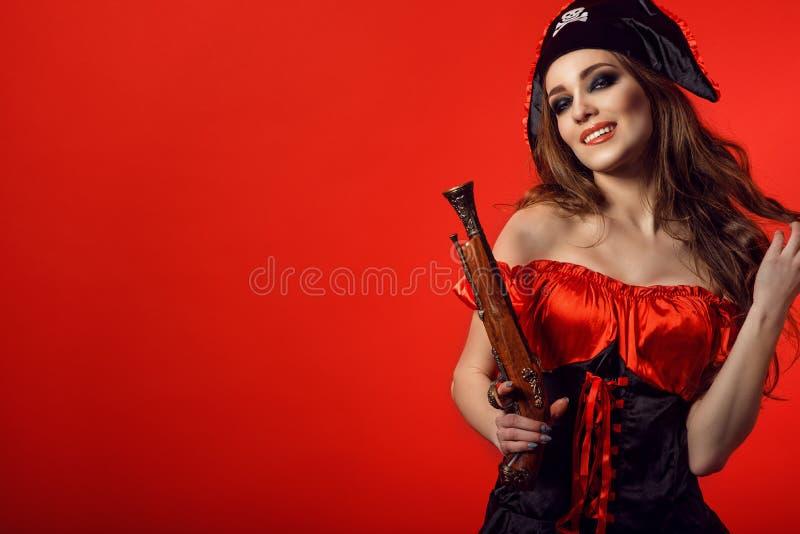 Retrato de la mujer atractiva magnífica con maquillaje provocativo que muerde su labio y que sostiene el arma de madera del vinta imagen de archivo
