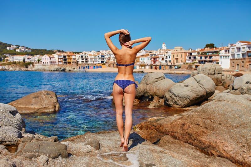 Retrato de la mujer atractiva que presenta en la playa de la costa de mar de Calella de Palafrugell, Cataluña, España cerca de Ba imagenes de archivo