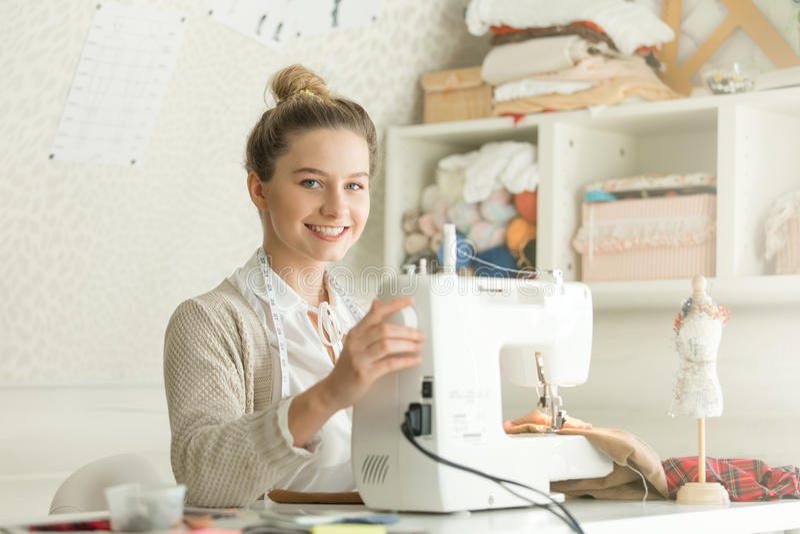 Retrato de la mujer atractiva sonriente en la máquina de coser foto de archivo libre de regalías