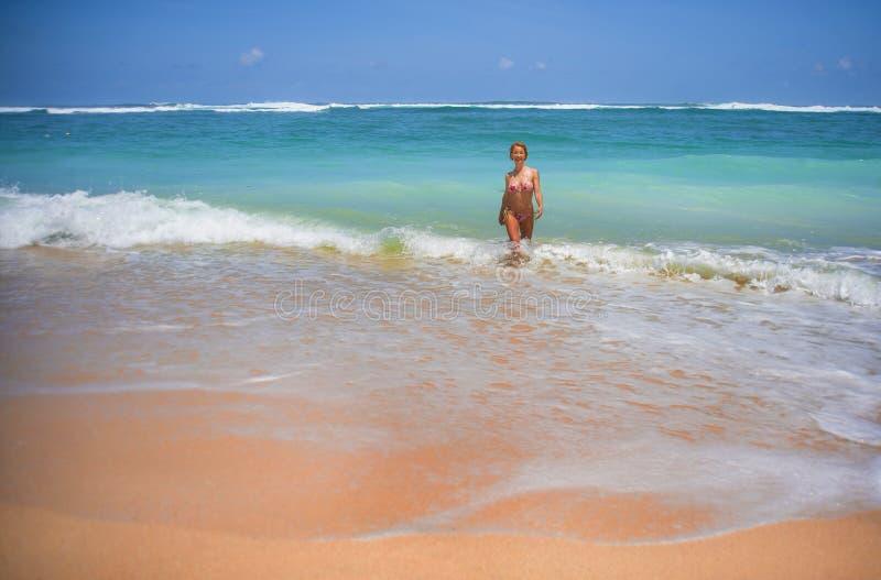 Retrato de la mujer atractiva y feliz joven en el bikini que presenta en sorprender la playa hermosa del desierto con el goce imp foto de archivo