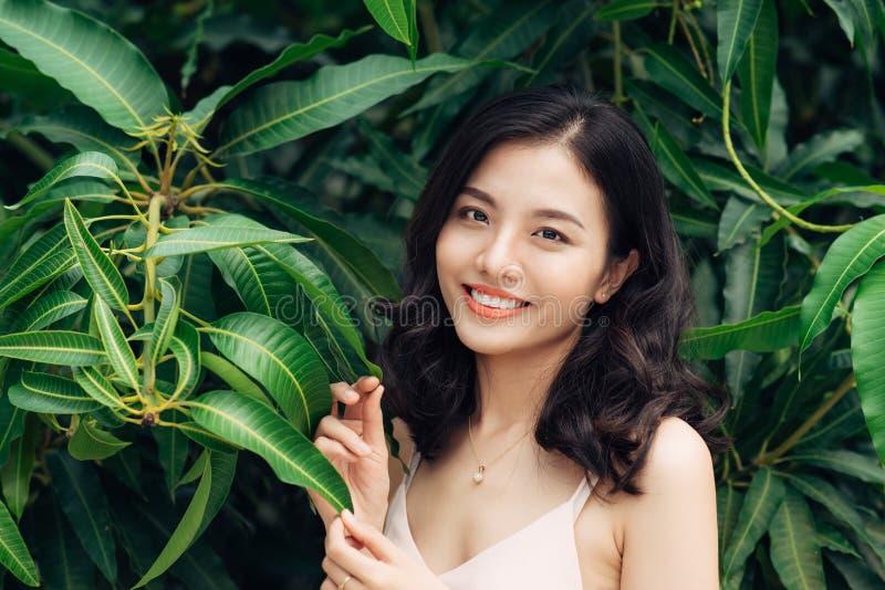 Retrato de la mujer bastante joven que se coloca cerca de las hojas al aire libre imagen de archivo libre de regalías