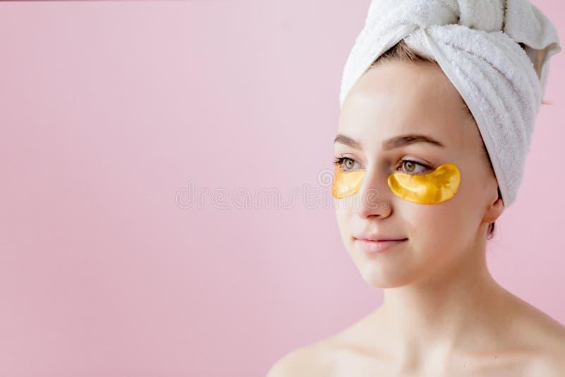 Retrato de la mujer de la belleza con los remiendos del ojo en fondo rosado Cara de la belleza de la mujer con la m?scara debajo  fotografía de archivo libre de regalías