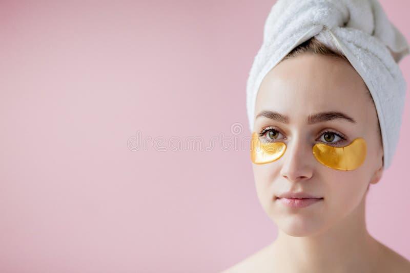 Retrato de la mujer de la belleza con los remiendos del ojo en fondo rosado Cara de la belleza de la mujer con la m?scara debajo  foto de archivo libre de regalías