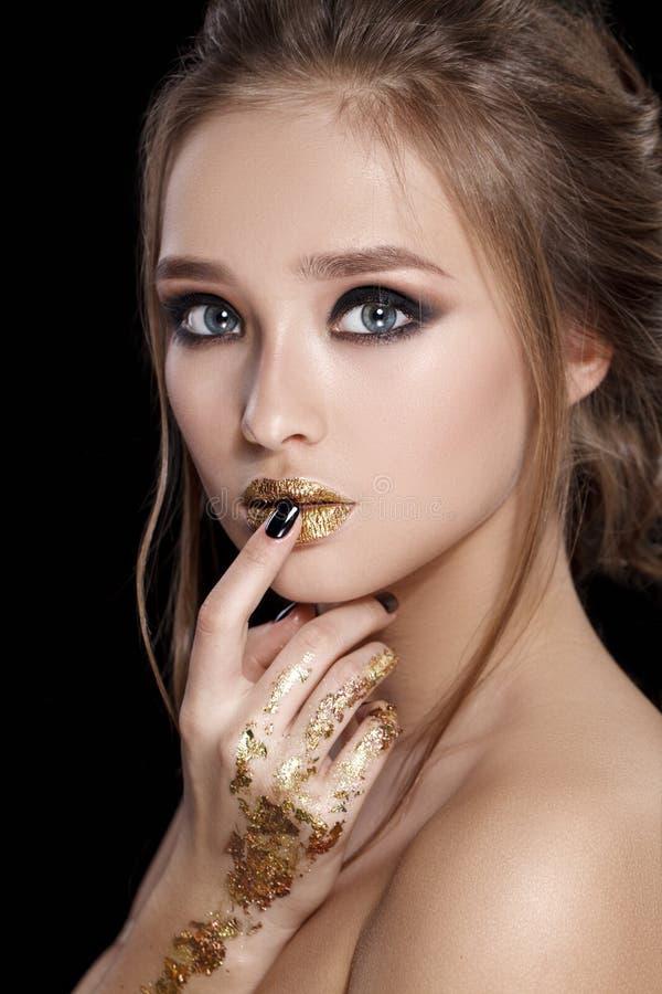 Retrato de la mujer de la belleza El maquillaje y la manicura profesionales con la hoja de oro brillan, los ojos del smokey Color fotografía de archivo libre de regalías