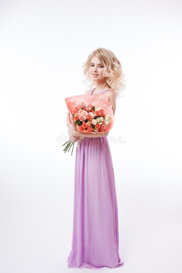 Retrato de la mujer blondy rizada hermosa con maquillaje perfecto Sostener el ramo Vestido púrpura de la tarde larga fotografía de archivo libre de regalías