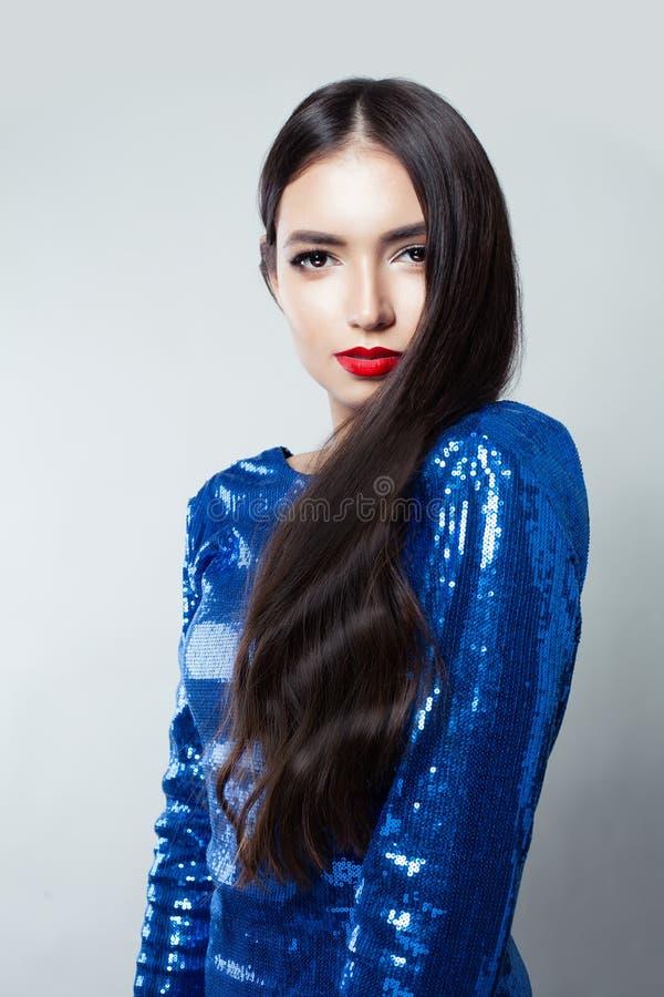 Retrato de la mujer bonita con el pelo largo y del maquillaje rojo de los labios contra el fondo blanco de la pared fotos de archivo