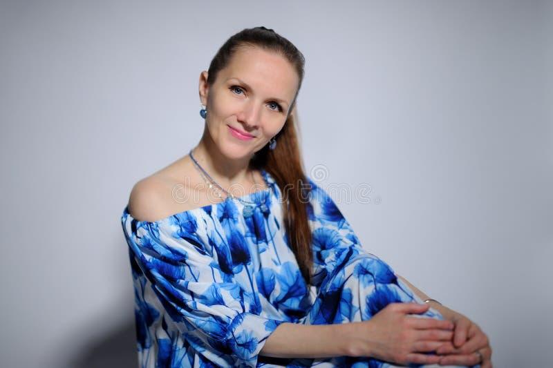 retrato de la mujer bonita en vestido azul sobre fondo gris foto de archivo libre de regalías