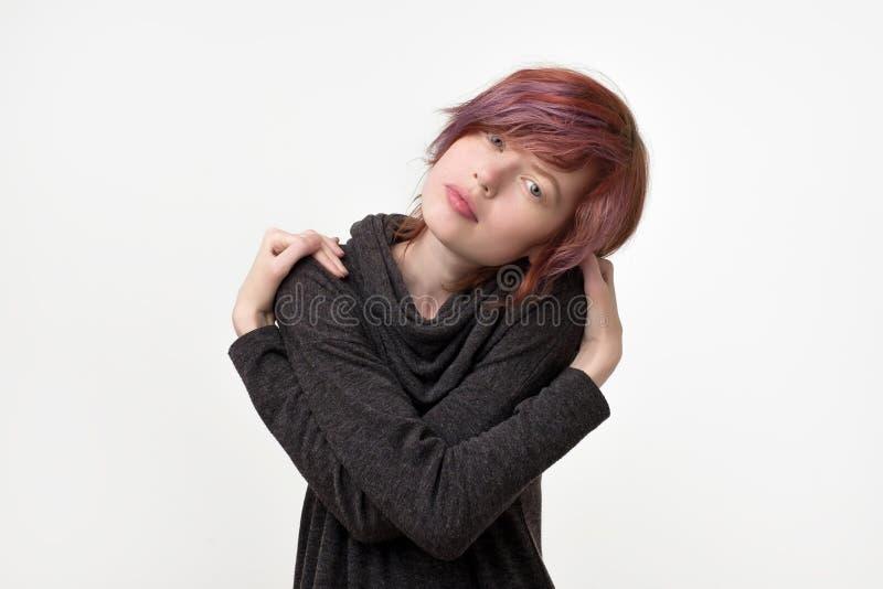 Retrato de la mujer bonita informal inusual con el peinado colorido que finge como ella se está abrazando Siendo orgulloso fotografía de archivo