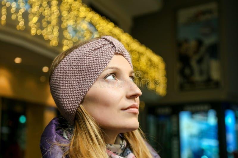 Retrato de la mujer bonita joven en venda de lana hecha punto hermosa al aire libre en el día frío del otoño Luces del bokeh de l imagenes de archivo
