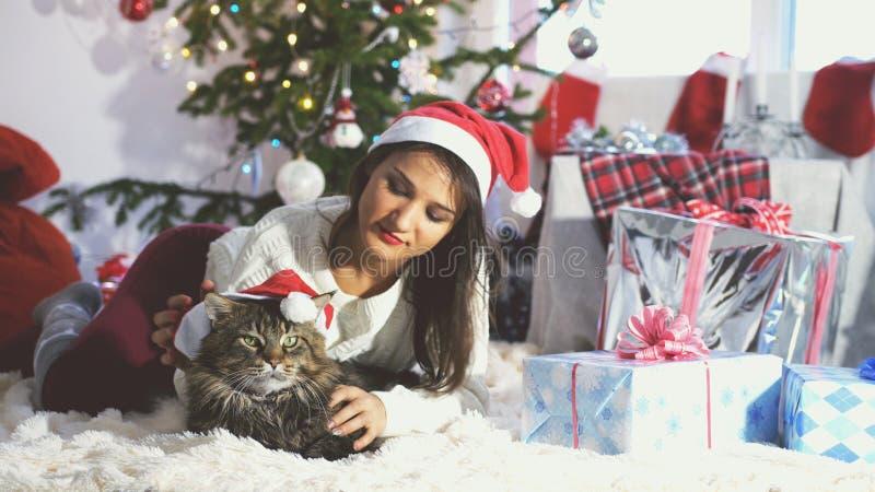Retrato de la mujer bonita joven que miente al lado del árbol de navidad en casa que juega con el gato de Maine Coon fotos de archivo libres de regalías